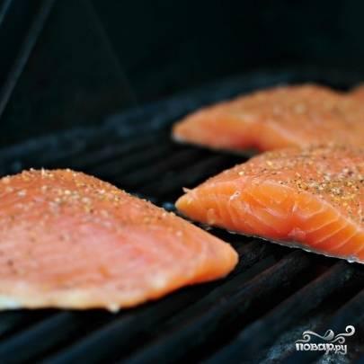 9. Приготовьте мангал. Можно жарить лосось и в духовке на решетке. Смажьте решетку оливковым маслом. Выложите кусочки лосося шкуркой вниз и жарьте в течение 5-6 минут.