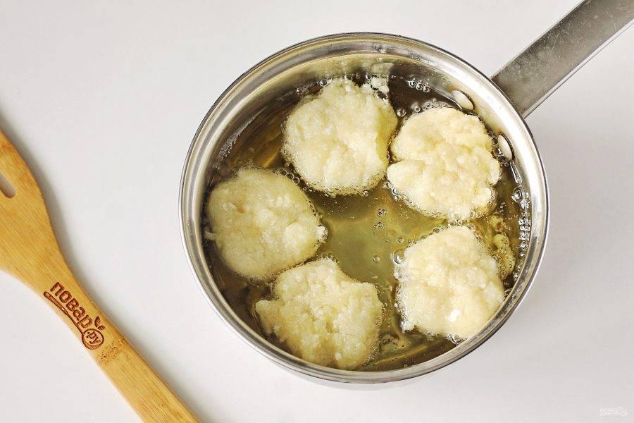 В кастрюльку небольшого диаметра налейте растительное масло и доведите его до кипения. Из теста формируйте руками шарики и поочередно бросайте их во фритюр.
