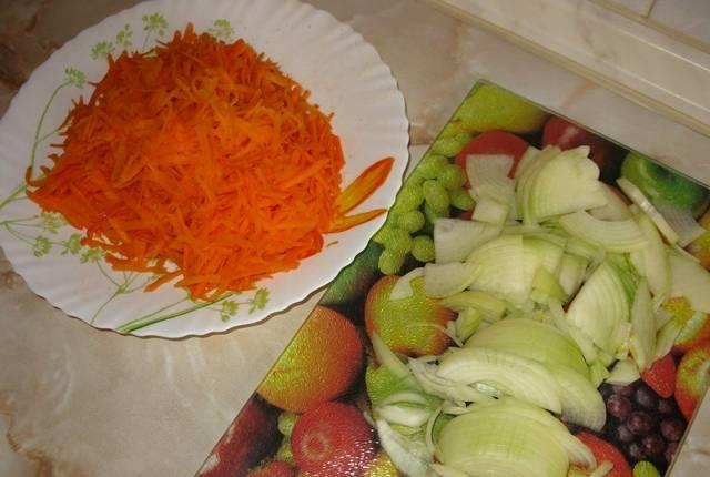 Чистим и промываем овощи, трем морковь на крупной терке, а репчатый лук нарезаем полукольцами.