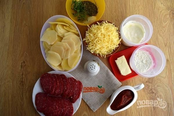 Подготовьте необходимые продукты. Картофель помойте и очистите. Колбасу и картофель нарежьте на тонкие ломтики. Сыр натрите на мелкой терке.