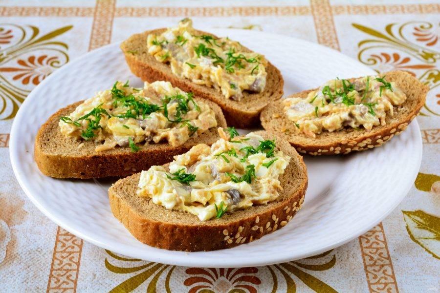 Кусочки ржаного хлеба намажьте селедочной начинкой, присыпьте рубленным укропом.