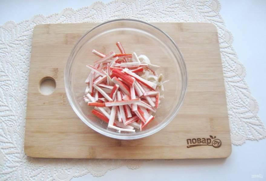 Добавьте крабовые палочки, нарезанные соломкой.