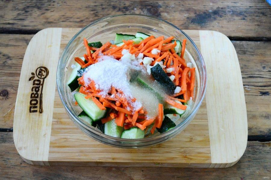 Смешайте огурцы и морковь в глубокой миске, добавьте сахар, соль, измельченный чеснок, растительное масло и уксус.