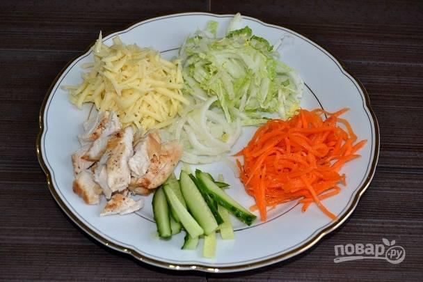 3. Готовую курочку немного остудите и нарежьте. Измельчите капусту, огурчик, натрите на терке сыр.