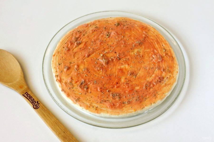 Соедините майонез и кетчуп. Смажьте основу для пиццы готовым соусом. Сверху посыпьте прованские травы.