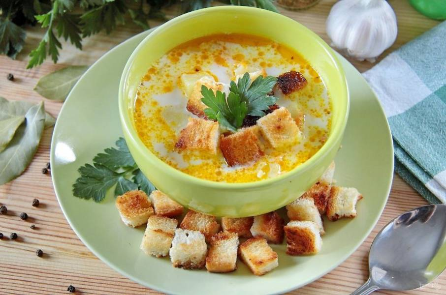 Суп с курицей, рисом и плавленым сыром готов. Подаем его в горячем виде, украсив каждую тарелку хрустящими гренками и свежей зеленью. Приятного аппетита!
