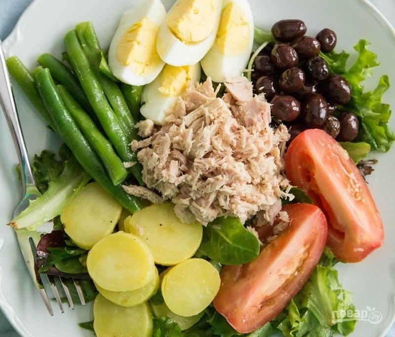 8. Для сборки салата: на блюдо выкладываю салатные листья, а на них уже кладу картофель, маслины, зеленую фасоль, яйца, томаты и по центру — немного тунца.