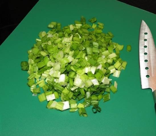 2. Следующим необходимо отправить в холодную воду рис (из расчета количества воды 2 к 1) и сварить до готовности. После закипания посолить по вкусу и при желании добавить любимые приправы к рису. Также нужно поставить варить яйца. Зеленый лук - довольно интересный ингредиент в начинке. Конечно, добавлять его не обязательно, однако он придает некую пикантность. Его нужно вымыть, просушить и мелко нарезать.