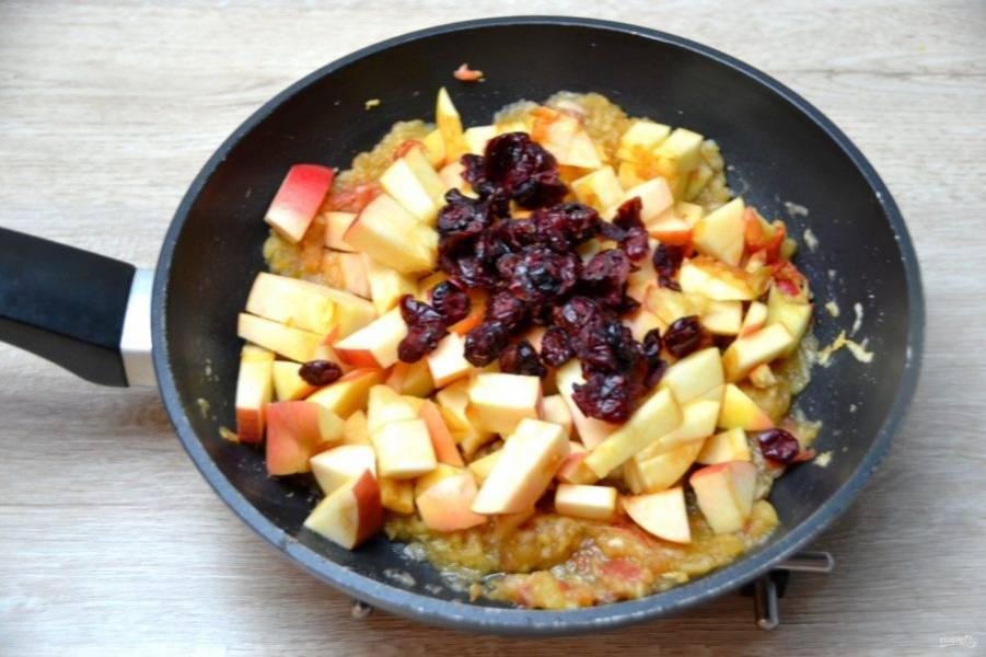 Добавьте яблоки нарезанные кусочками, всыпьте вяленую клюкву, продолжайте тушить.