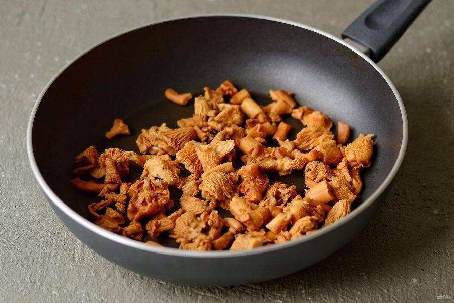 Разогрейте сухую сковороду на среднем огне. Выложите лисички, посолите и дождитесь, пока грибы начнут выделять сок. Слейте его. Повторите несколько раз.