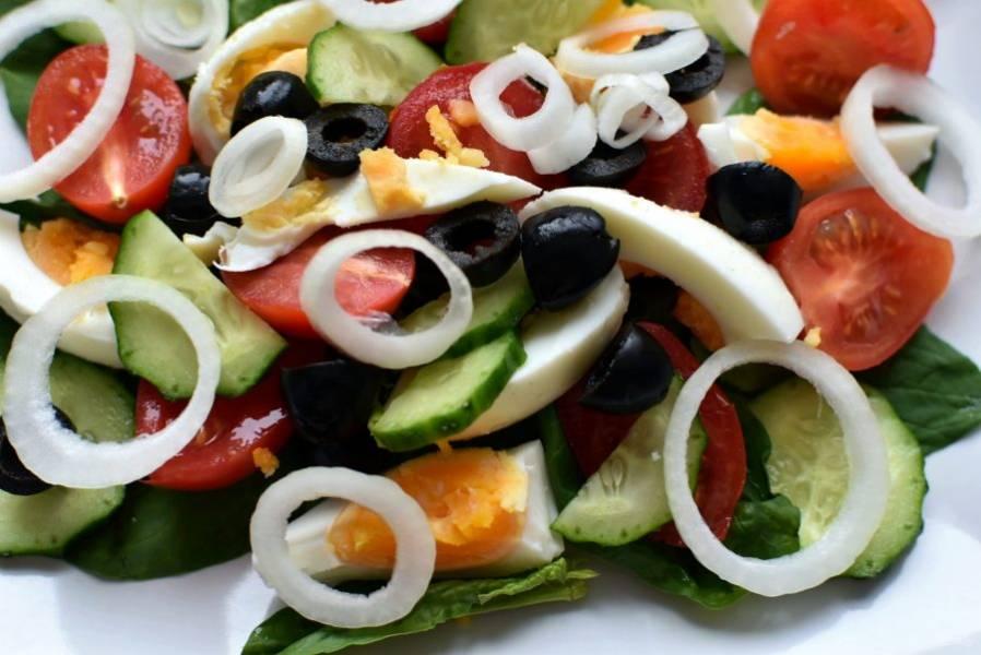 На тарелку выложите шпинат, сверху разложите нарезанные восьмушками яйца, половинки помидоок черри, половинки маслин, тонкие кружочки лука и огурца.