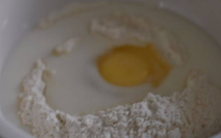 Для приготовления теста в глубокую посуду всыпать горкой муку. В середине горки сделать углубление, вбить в него яйцо, влить молоко.