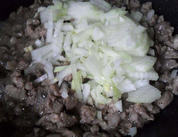 Обжариваем мясо на сковороде с растительным маслом, солим и перчим. Затем добавляем мелко нарезанный лук, обжариваем все вместе минут 5-7.