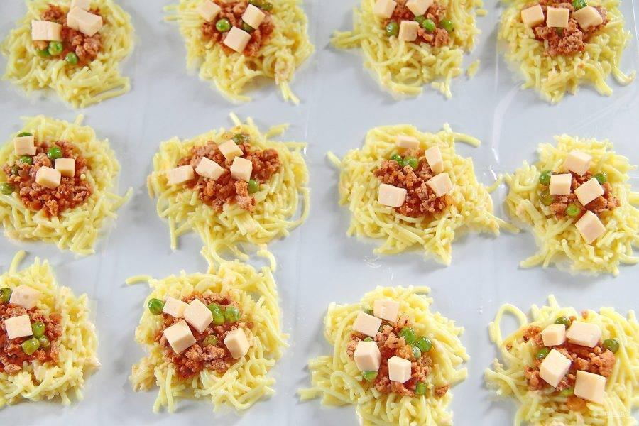 Для того чтобы приготовить аранчини, застелите стол пищевой пленкой. Я использую рукав для запекания. Распределите пасту в форме небольших лепешек. По центру положите немного фарша и нарезанный кубиками сыр.