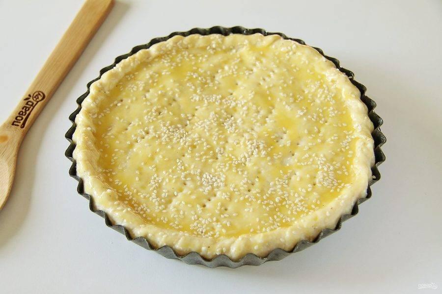 Защипните края, сделайте сверху проколы вилкой для выхода пара, смажьте тесто яичным желтком и посыпьте кунжутом. Выпекайте в духовке при температуре 190 градусов в течение 30 минут.
