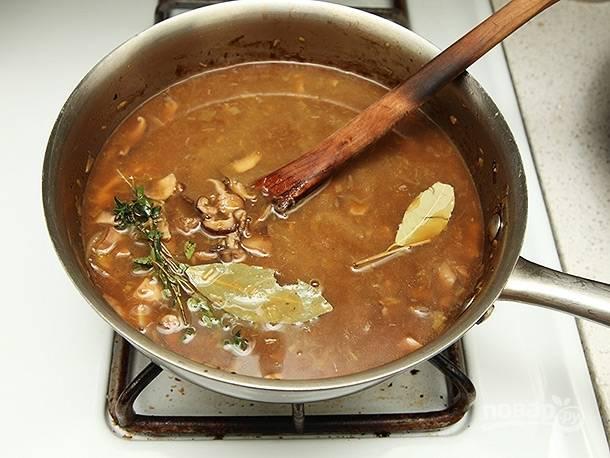 Когда вино немного выпарится, добавьте бульон, лавровый лист и веточку тимьяна. Варите суп на медленном огне в течение 30 минут.