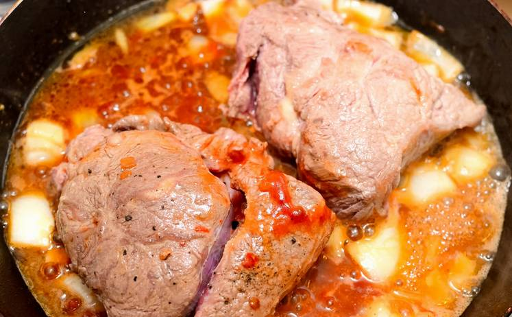 2. Лук режем средними кусочками, добавляем к мясу. Когда уже и лук, и мясо станут румяными, уменьшаем огонь, вливаем бульон и томатную пасту. Перемешаем и тушим, пока лишняя вода не уйдет. Затем переворачиваем ромштексы, посыпаем сыром и кусочками ананаса, под крышкой держим до готовности.