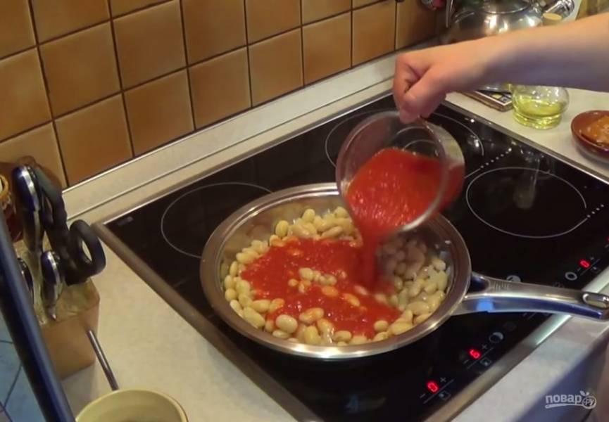 2. Добавьте отваренную фасоль и слегка потушите с луком. Затем добавьте томатное пюре и доведите до кипения. Уменьшите огонь и потушите фасоль 15 минут, не накрывая ее крышкой.