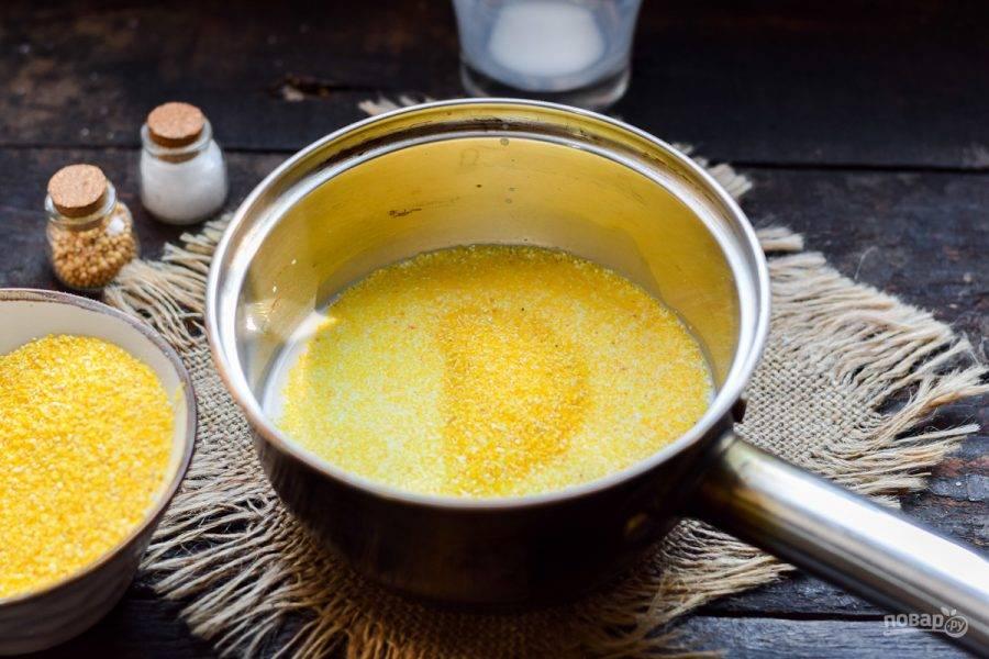 Всыпьте кукурузную крупу в кастрюлю. Поставьте кашу на умеренный огонь.