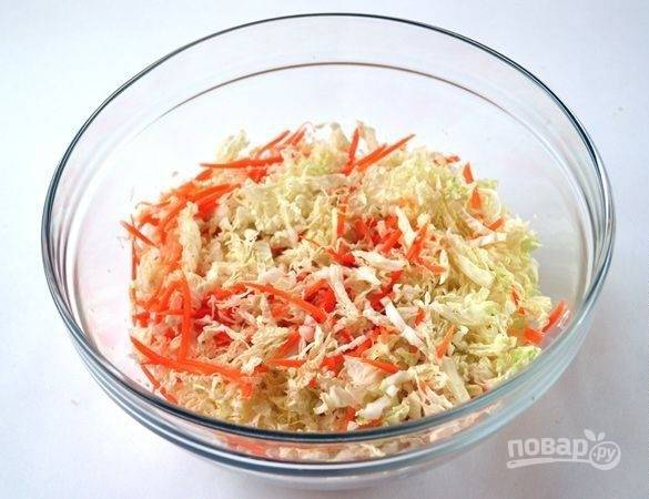 В салатнице соедините морковь и капусту. Посолите овощи, а затем хорошо размешайте и придавите, чтобы пошёл сок.