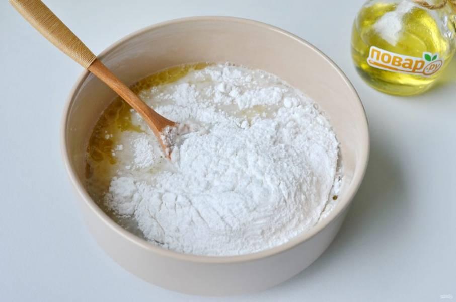 4. Частями добавьте рисовую муку, после каждого стакана тщательно перемешивая. Консистенция теста средней густоты, чуть гуще сметаны, хотя выглядит более плотным, но ложкой легко замешивается.