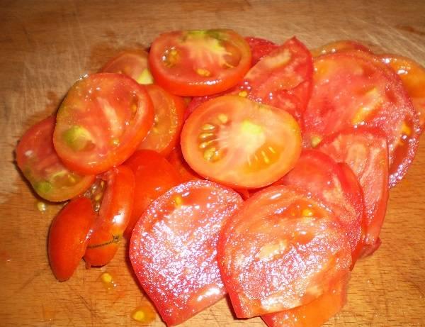 2. Помидоры вымыть, обсушить и нарезать кружочками. В рецепт приготовления пиццы по-быстрому с ветчиной можно использовать также маринованные огурчики, если помидоров нет под рукой.