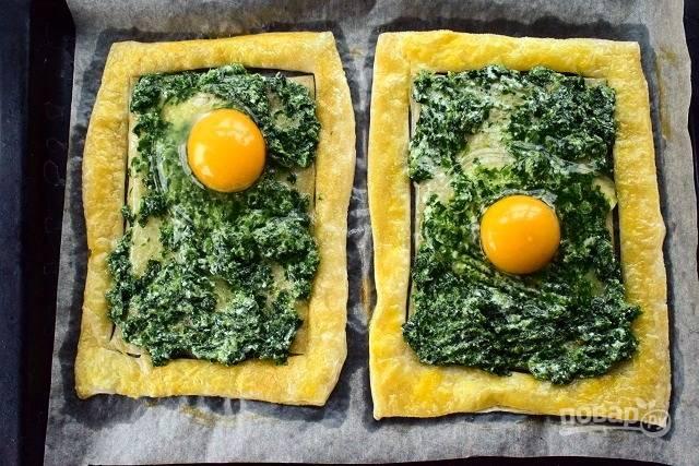 Соедините со сметаной. Разложите начинку по запеченным заготовкам, не заходя на бортики. Сверху разбейте по 1-2 яйца и отправьте будущий пирог в духовку запекаться на 7 или 12 минут. Время запекания зависит от ваших предпочтений по запеканию яйца.