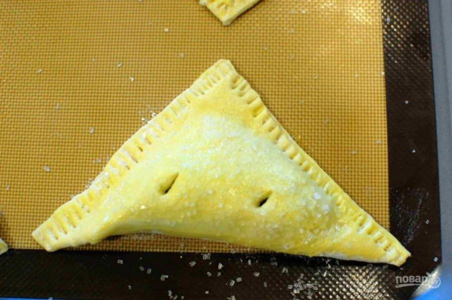 8.Посыпьте слойки крупным сахаром и с помощью ножа проделайте в каждой по два отверстия.