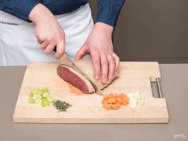 1. Подготовьте овощи. Нарежьте кубиками морковь, сельдерей и лук. Измельчите розмарин, тимьян и чеснок. Мясо нарубите средними кусочками. Затем в сотейнике разогрейте масло. Обжарьте в нём в течение 5 минут сельдерей, лук, морковь, корицу, травы, чеснок и лавровый лист.
