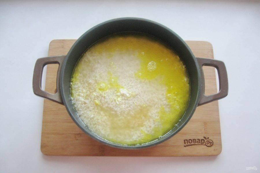 Затем выложите рис в казан и залейте горячей водой на 1-1,5 пальца выше риса. Казан не накрывайте крышкой и готовьте плов на среднем огне 10-15 минут, пока вода сверху уже выпарится, но по бокам и внизу казана еще остается.