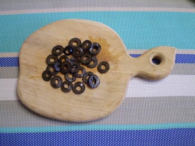 11. Маслины без косточек режем тонкими колечками.