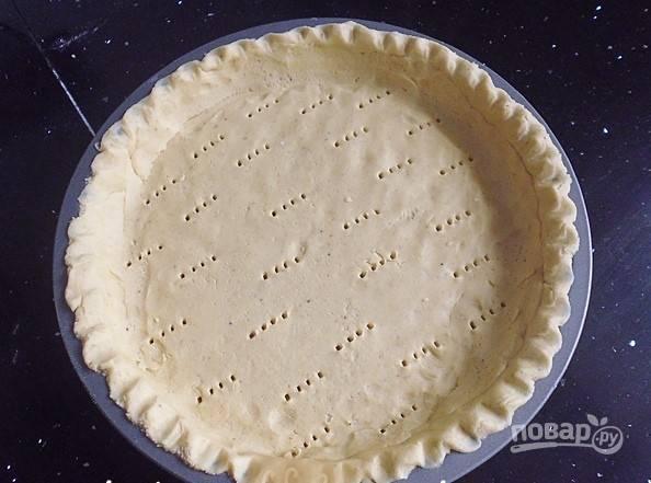Руками уложите тесто в форму, распределите равномерным слоем. Сделайте проколы вилкой, сверху застелите бумагой для выпечки и всыпьте фасоль. Отправьте в разогретую до 160 градусов духовку на 15 минут.