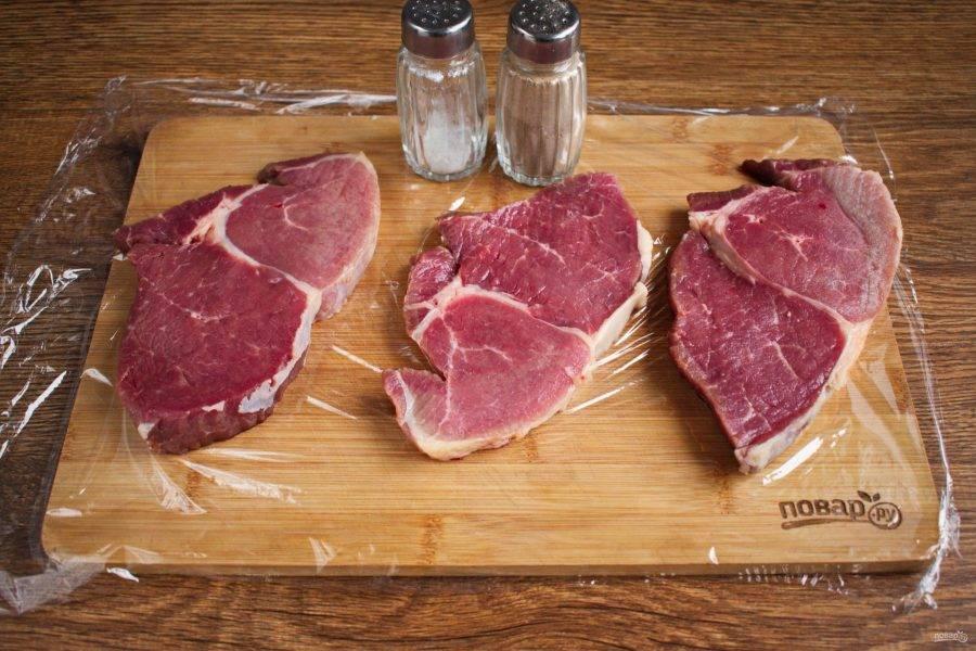 Достаньте мясо из холодильника, по меньшей мере, за 45-60 минут до готовки. Стейки обсушите бумажными полотенцами, посолите и поперчите с двух сторон, слегка вотрите соль и перец пальцами в мясо.