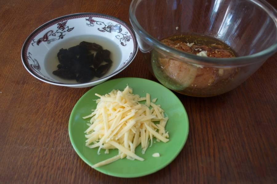 Натрите на терку твердый сыр. В неширокую миску влейте оливковое масло, соевый соус, добавьте специи, выдавите через пресс чеснок, добавьте все специи по вашему вкусу. Поместите в маринад мясо и маринуйте его 30 минут.