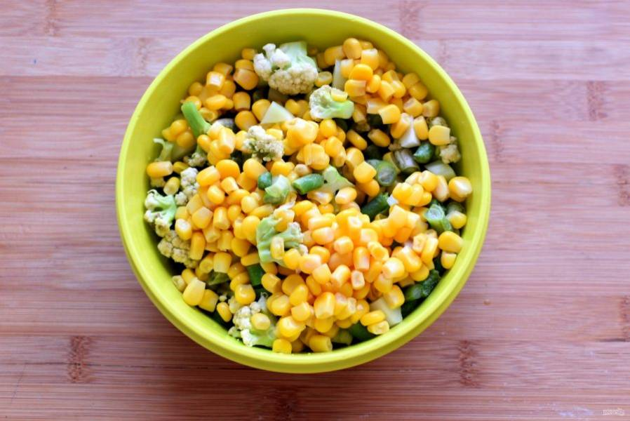 Добавьте разобранную на мелкие соцветия капусту, нарезанную зеленую фасоль и кукурузу. Отправьте в суп мелко нарезанный лук и сладкий перец - кубиками. Варите еще 2 минуты.