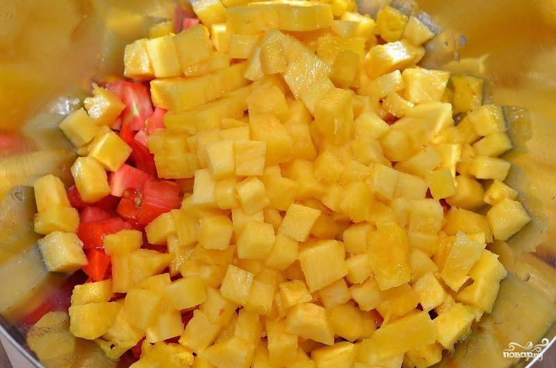 Из ананаса вырезаем сердцевину, нарезаем ее кубиками такого же размера и смешиваем с помидорами.