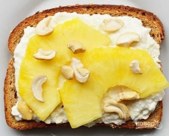 На следующий ломтик разложите творог. Сверху разрезанный пополам ананас и орешки кешью.