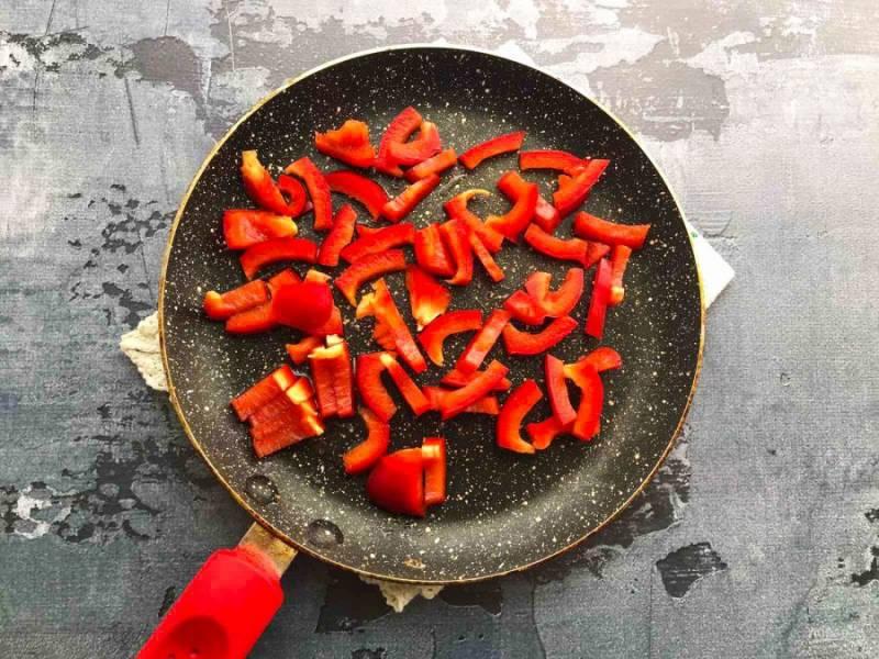 Перец хорошо помойте под проточной водой, очистите от семян, нарежьте небольшими кусочками и обжарьте на хорошо разогретой сковороде с растительным маслом в течение 4-5 минут.