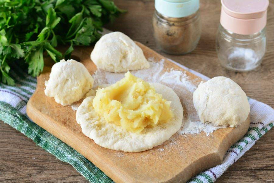 Тесто разделите на небольшие шарики, каждый придавите ладошкой или раскатайте слегка скалкой, выложите в центр 1 ложку картофельной начинки.