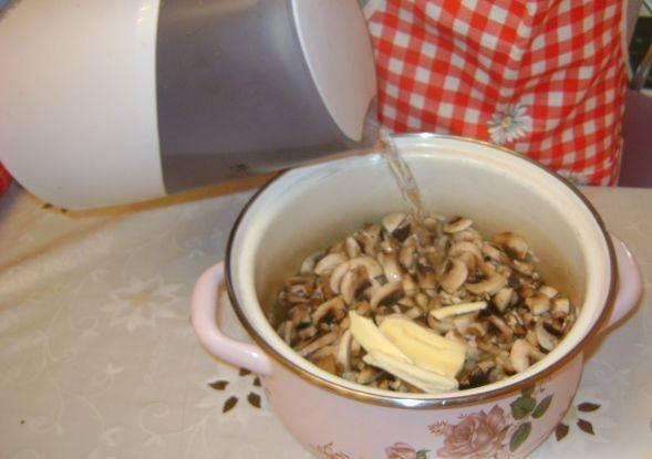 Рис промойте и смешайте с нарезанными шампиньонами, добавьте сливочное масло. Затем залейте воду (чтобы слегка все покрывала) и тушите на среднем огне.