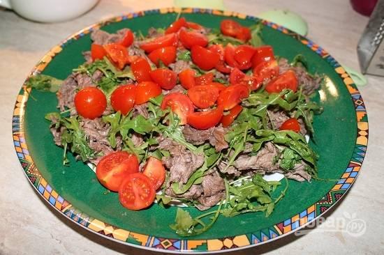 Перекладываем мясо на блюдо, поверх выкладываем дольки помидоров.