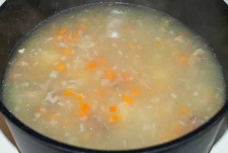 По истечении 2 часов, мы аккуратно извлекаем кости из бульона и отделяем от них мясо, бульон процеживаем и возвращаем в кастрюлю. Когда жидкость снова закипит, выкладываем в бульон кусочки мяса, добавляем рис (предварительно промытый) и нарезанные овощи, солим и приправляем все специями по вкусу. Варим суп еще 20-25 минут, после чего снимаем с огня.