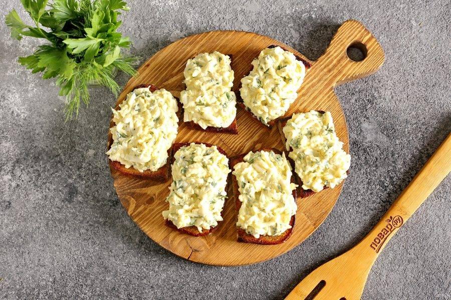 Нанесите на обжаренную сторону хлеба, натертую чесноком, яичную массу.