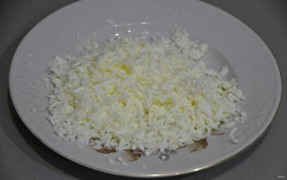 Очистите яйца, отделите желтки, белки натрите на крупной терке.