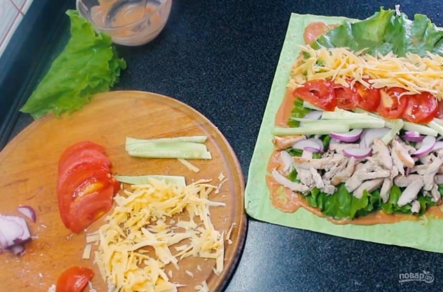 2. Приготовьте соус: горчицу смешайте со сметаной и томатной пастой. Смажьте лаваш соусом. Выложите листья салата и начинку, чередуя ее.