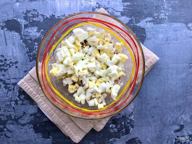 Вареные яйца очистите от скорлупы, мелко нарежьте и добавьте к курице.
