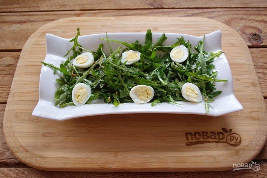 На блюдо для подачи салата выложите заправленную рукколу. Отварите перепелиные яйца до готовности.