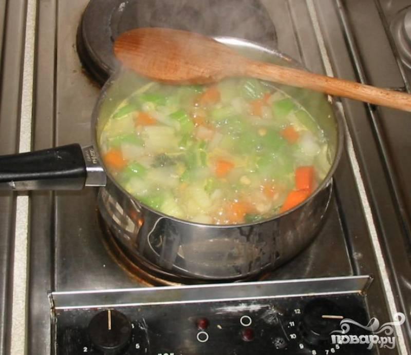 3.Сложить все овощи, горох, петрушку и чеснок в кастрюлю, залить бульоном и довести до кипения. Уменьшить огонь, чтобы суп едва кипел. Готовить суп 1 час – 1 час 15 минут, пока овощи не станут мягкими.