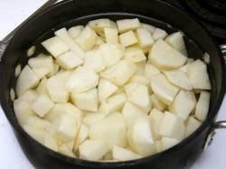 Для начала помойте и почистите картошку. Затем нарежьте кубиками и переложите в кастрюлю, залейте водой так, чтобы покрыло слой картофеля.