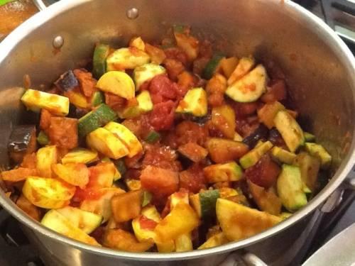 Берем кастрюлю, туда выкладываем все содержимое сковороды и к нему добавляем оставшиеся овощи. Перчим, солим их и перемешиваем. Заливаем водой так, чтобы она полностью закрыла овощи. Накрываем кастрюлю крышкой и тушим около получаса. До того пока баклажан не станет мягким.